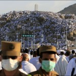 Saudi police secure the street as Muslim pilgrims pray on a rocky hill called the Mountain of Mercy, on the Plain of Arafat near Mecca, Saudi Arabia, Sunday, Dec. 7. Nearly 3 million pilgrims converged Saturday around the holy city of Mecca at the beginning of the 5-day hajj pilgrimage, a lifelong dream for many Muslims. AP / Hassan Ammar