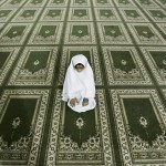 "A Palestinian Muslim girl prays in the men's mosque before the evening prayer called ""tarawih"", during the holy fasting month of Ramadan in the West Bank city of Ramallah, Wednesday, Sept. 17, 2008. (AP Photo/Muhammed Muheisen) #"