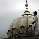 A Pakistani man offers Friday prayers atop a mosque roof during the holy Muslim month of Ramadan in Peshawar, Pakistan on Friday, Sept. 5, 2008. (AP Photo/Mohammad Sajjad) #