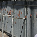 Palestinian women walk past men (on the other side of the fence) waiting to cross a checkpoint to get into Israel in order to pray for the holy fasting month of Ramadan at the Al Aqsa Mosque in Jerusalem's Old City, in the West Bank town of Bethlehem, Friday, Sept. 12, 2008. (AP Photo/Tara Todras-Whitehill) #
