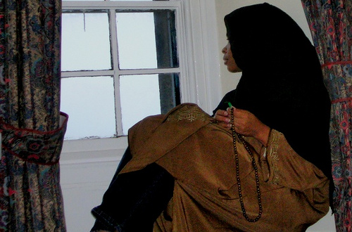 An African American Muslim woman sitting at a window