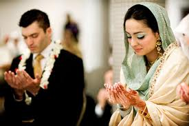 Muslim couple saying a dua' (prayer) at their wedding.