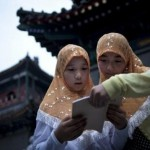 Two Muslim Chinese girls reading a book of prayers.