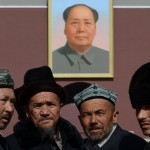 Uighur Muslims in front of a portrait of the Chinese president.