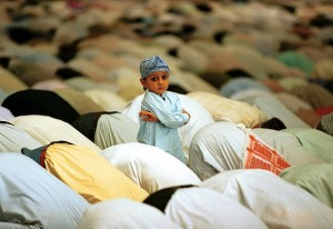 small boy standing amid worshipers in salat 300x206 %photo