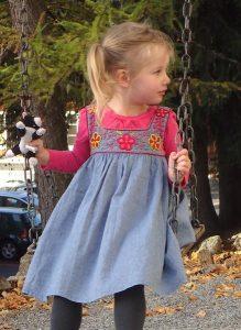 Little girl sitting on a swing