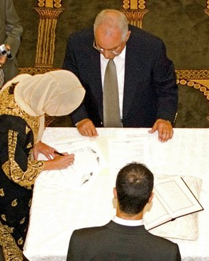 A Muslim bride signing the Islamic marriage contract.