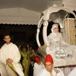 The bride and groom enter the wedding hall - Hakima wearing a splendid silver dress and carried aloft on a silver wedding chair, and Si Mohamed on horseback