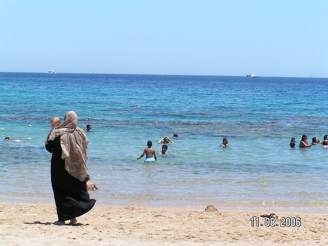 Muslim woman and baby on beach