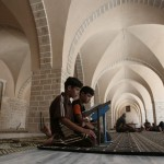 Palestinian boys read the Quran at the al-Omari mosque in Gaza City during Ramadan