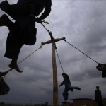 Afghan refugee boys in Islamabad play on a home made swing during Eid al-Fitr 2011