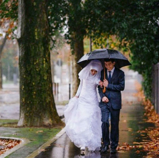 Young Muslim couple sharing an umbrella.